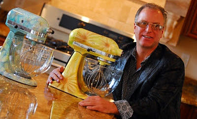 Loucks proudly displays a couple of his hand-painted Kitchen-Aid mixers. (Photo courtesy The Art of Design.)