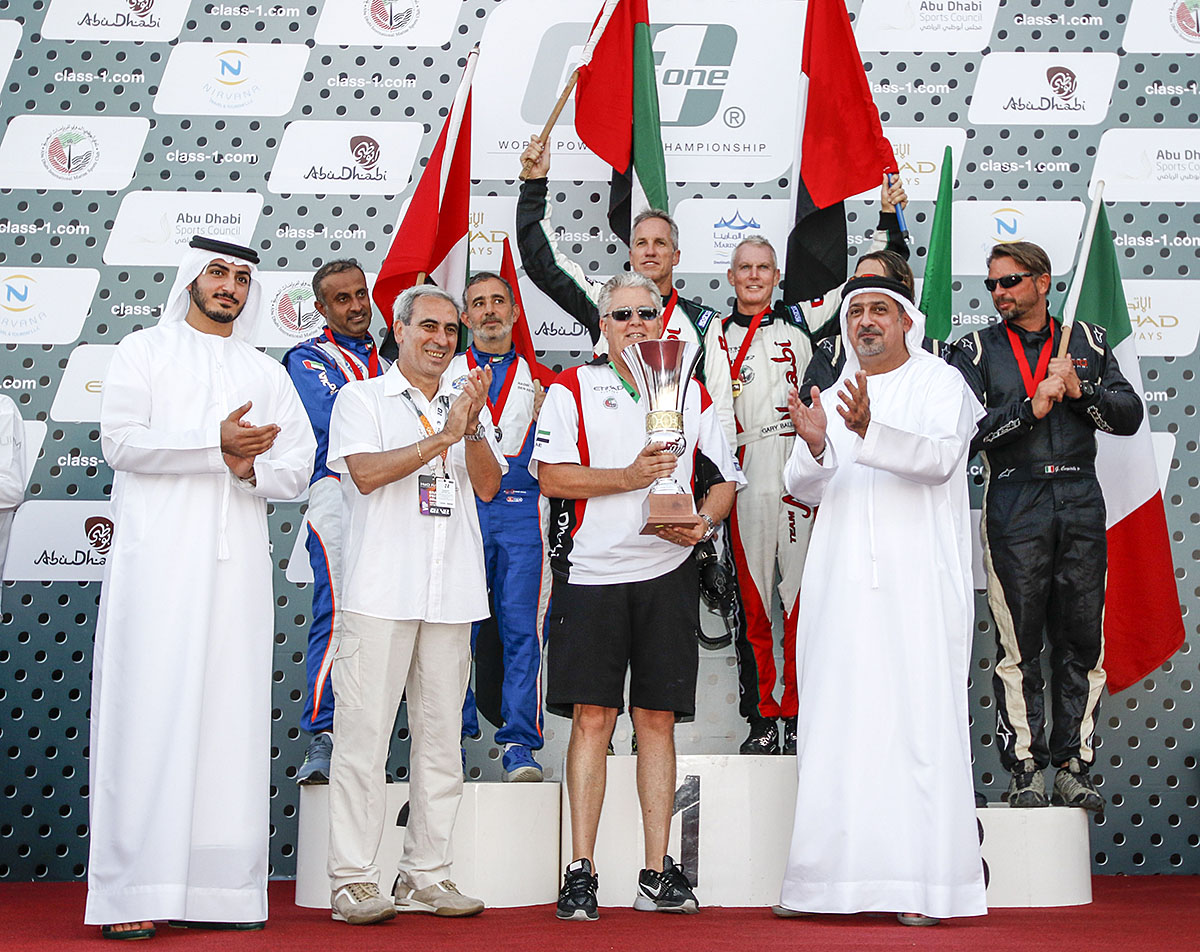 Team Abu Dhabi manager Randy Scism accepts the Class 1 world championship trophy after Gary Ballough and John Tomlinson (top of podium) drove the Mercury Racing-powered 48-foot to the championship. Photo by Simon Palfrader