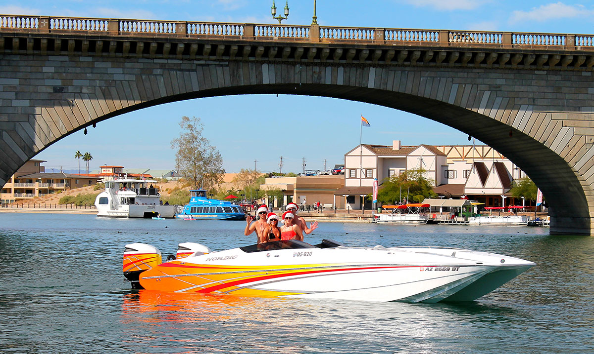 Like Mike Tracy and his crew in his Nordic Boats 29 Deck Boat, many Monster Bash Poker Run attendees take holiday photos in front of the London Bridge in Lake Havasu City, Ariz. Photo courtesy Mike Tracy