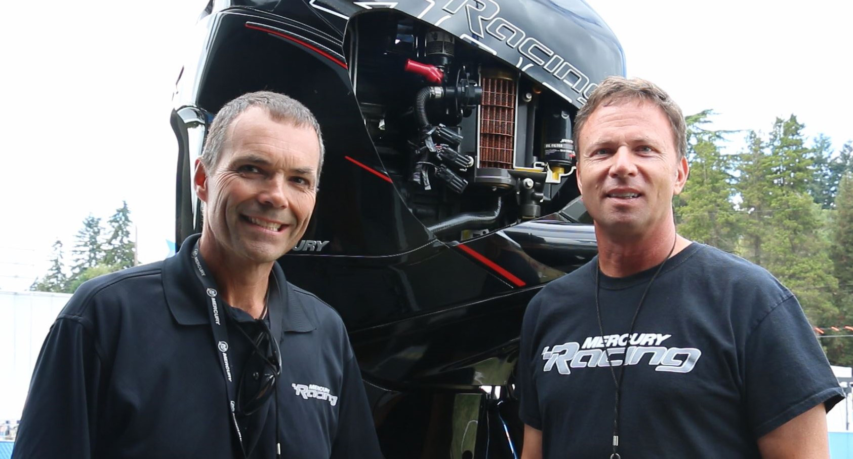 Mercury Racing's Rick Mackie and propeller program manager Scott Reichow in front of the display vehicles Verado 400R outboard cutaway.